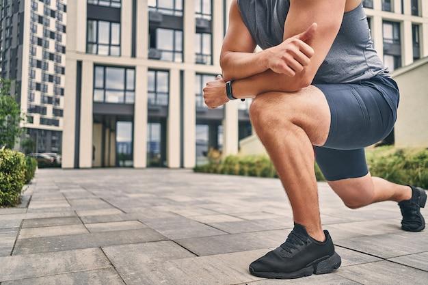 Closeup perna e braço de homem musculoso em tênis e shorts durante o aquecimento ao ar livre
