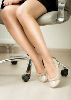 Closeup pernas de mulher de negócios sexy sentadas na cadeira do escritório