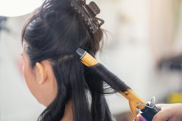 Closeup pessoas cabeleireiro cabeleireiro faz penteado na loja de corte de cabelo, cuidados com os cabelos no salão spa moderno