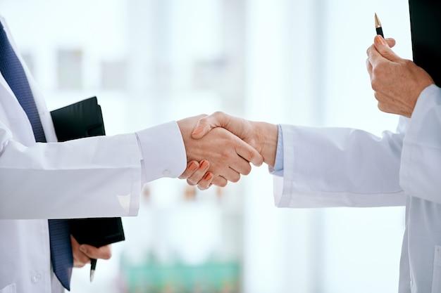 Closeup pessoas em jalecos brancos apertando as mãos