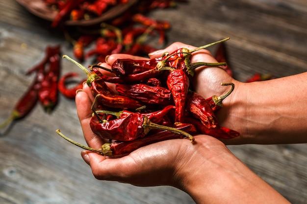 Closeup pimenta mexicana seca nas mãos sobre uma mesa de madeira