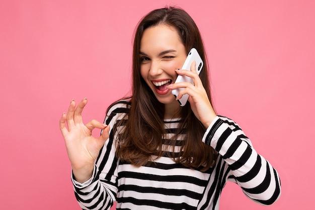 Closeup piscando mulher jovem muito feliz falando ao telefone, vestindo uma blusa listrada isolada por cima da parede com espaço de cópia, mostrando um gesto ok.