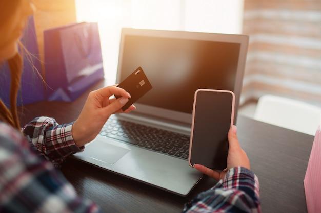Closeup plano laptop smartphone e cartão de crédito nas mãos. conceito de compras on-line e entrega em domicílio.