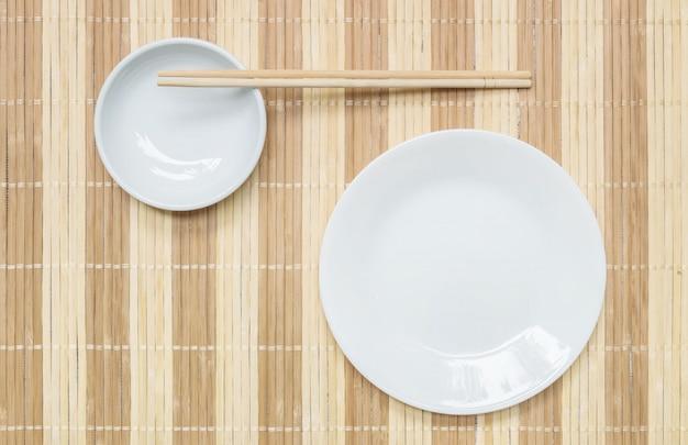 Closeup prato de cerâmica e cálice com pauzinhos de madeira sobre fundo de esteira de madeira
