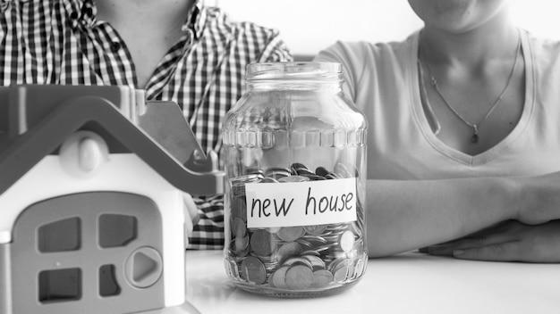 Closeup preto e branco vista de um jovem casal sentado à mesa branca em que está localizada uma pequena casa e, cheia de moedas, o frasco com a inscrição nova casa