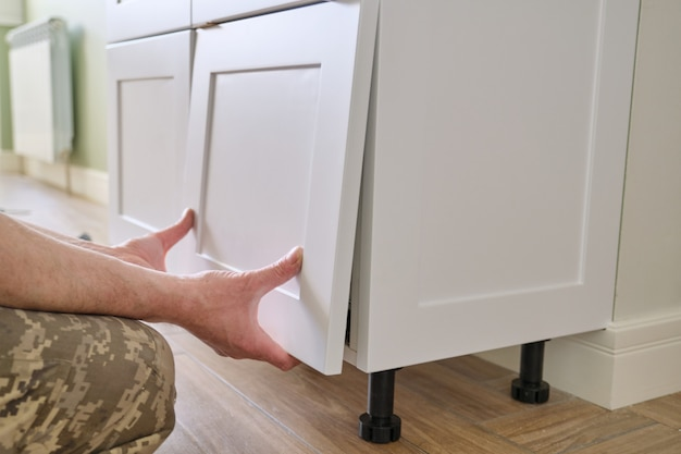 Closeup processo de montagem de móveis de cozinha, mãos de trabalhador masculino