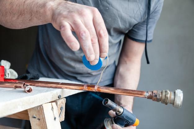 Closeup profissional encanador mestre segurando pasta de fluxo para soldar e soldar costuras de queimador de gás de tubulação de cobre.