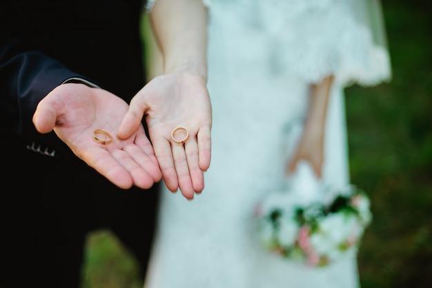 Closeup recém-casados mostram seus anéis de casamento