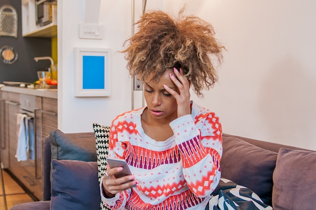 Closeup retrato chateado triste, cético, infeliz, séria mulher africana falando no telefone. emoção humana negativa sentimento de expressão facial, reação da vida. más notícias