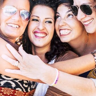 Closeup retrato com quatro mulheres jovens com rostos unidos e se divertindo muito juntos, sorrindo como um louco -