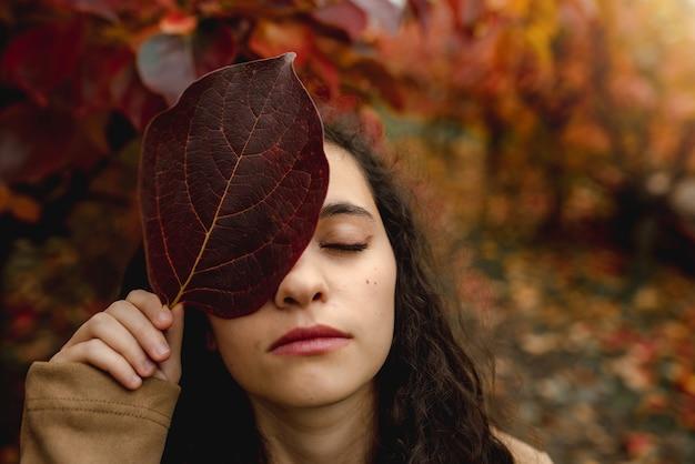 Closeup retrato com rosto de mulher com os olhos fechados, cobrindo os olhos com uma folha vermelha caída.