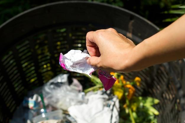 Closeup retrato cortado de alguém jogando pedaço amassado de pacote de plástico de sorvete na lata de lixo, isolado ao ar livre fundo de árvores verdes