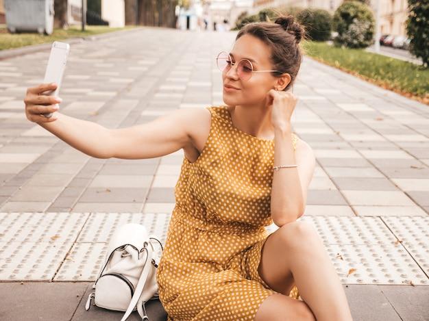 Closeup retrato da bela menina morena sorridente no verão hipster amarelo vestido. modelo tirando selfie no smartphone. mulher fazendo fotos em dia de sol quente na rua em óculos de sol