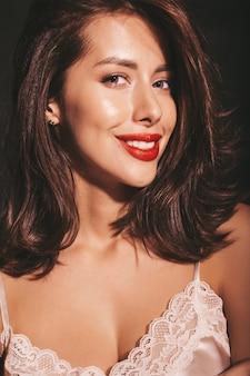Closeup retrato da bela mulher morena sensual sorridente. garota com roupas clássicas bege elegantes. modelo com os lábios vermelhos isolados no preto