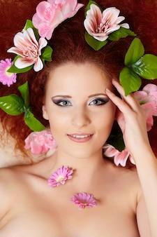 Closeup retrato da bela ruiva sorridente rosto de mulher ruiva com flores coloridas no cabelo tocando o rosto