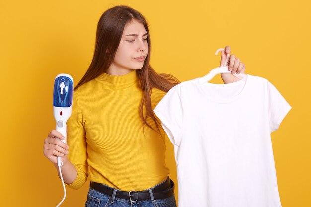 Closeup retrato da encantadora mulher com cabelos longos, segurando os cabides com camiseta casual branca.