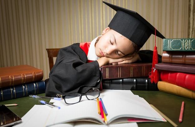 Closeup retrato da menina adormecida com o chapéu da formatura deitada na mesa cheia de livros
