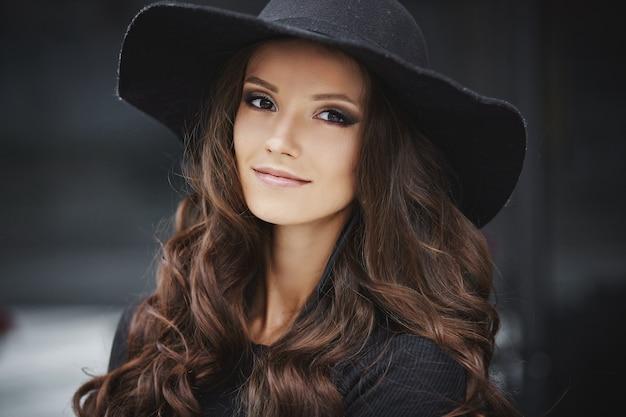 Closeup retrato da moda de uma jovem modelo com maquiagem da moda e chapéu preto da moda posando ao ar livre