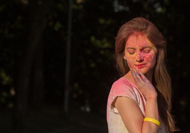 Closeup retrato da modelo linda morena coberta com pó colorido, posando no festival de holi