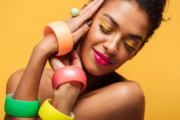 Closeup retrato da mulher afro-americana de moda com maquiagem brilhante e acessórios multicoloridos de mãos dadas no rosto, isolado sobre parede amarela