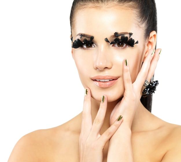 Closeup retrato da mulher bonita com maquiagem de cílios postiços pretos longos e unhas douradas. isolado em fundo branco