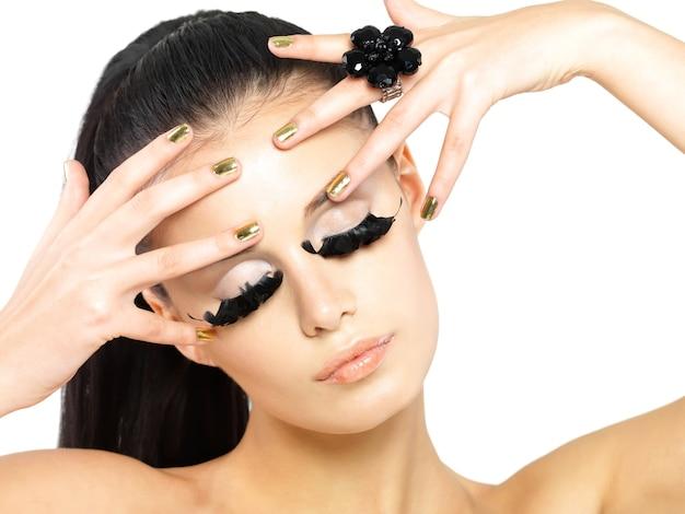 Closeup retrato da mulher bonita com maquiagem de cílios postiços pretos longos e unhas douradas. isolado na parede branca