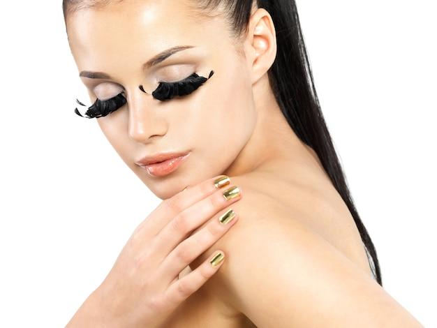 Closeup retrato da mulher bonita com maquiagem de cílios postiços pretos longos e unhas douradas.