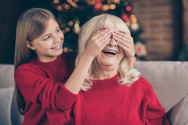 Closeup retrato da neta fechando os olhos da avó surpresa na casa decorada