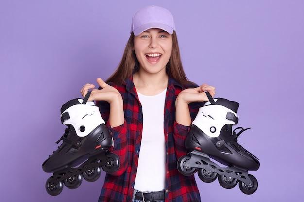 Closeup retrato de adorável garota encantadora com patins nas mãos