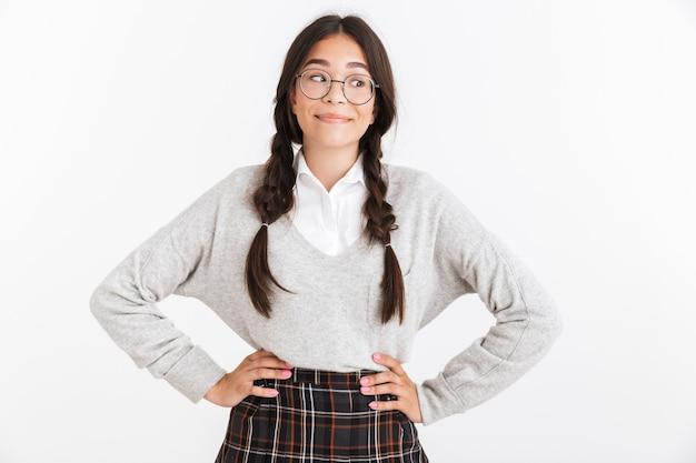 Closeup retrato de alegre adolescente usando óculos e uniforme escolar, sorrindo para a câmera isolada sobre a parede branca