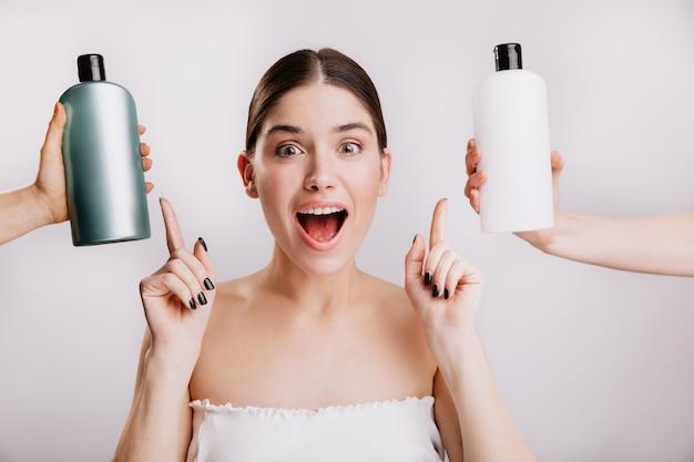 Closeup retrato de alegre garota posando sem maquiagem na parede branca. a mulher escolhe qual shampoo é melhor usar.