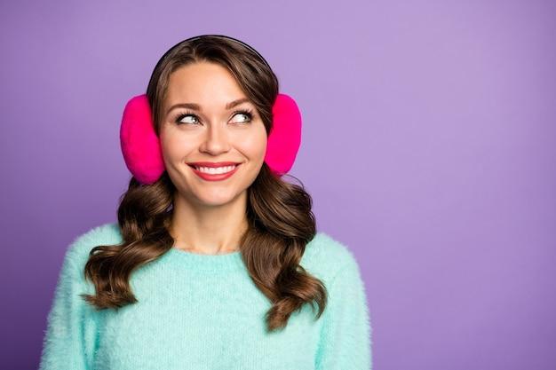 Closeup retrato de atraente senhora bonita engraçada de bom humor procurando lado espaço vazio interessado usar tampas de ouvido quentes casuais de pulôver fofo rosa pastel.