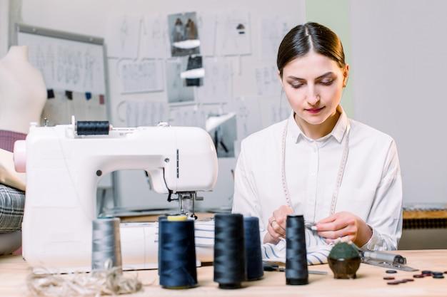 Closeup retrato de costureira de mulher jovem e bonita sentada e costura na máquina de costura em sua oficina. costureira trabalhando na máquina de costura.