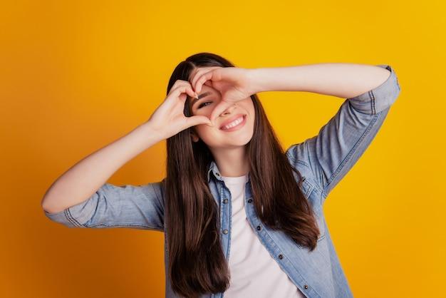 Closeup retrato de dedos de mulher mostra gesto de coração, olhar, olhar, capa, olhos, isolado, parede amarela, fundo