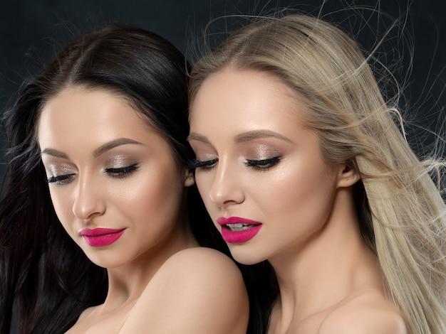 Closeup retrato de duas belas mulheres jovens sobre a parede preta. batom rosa brilhante. conceito de cuidados com a pele, cosméticos, terapia spa ou cosmetologia