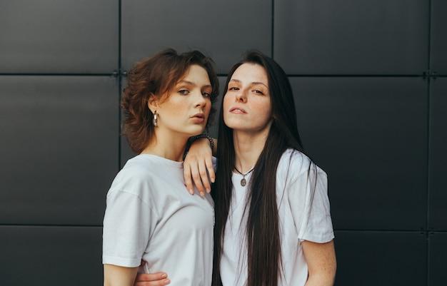 Closeup retrato de duas garotas atraentes em camisetas brancas