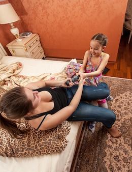 Closeup retrato de duas garotas lutando pelo controle remoto da tv na cama