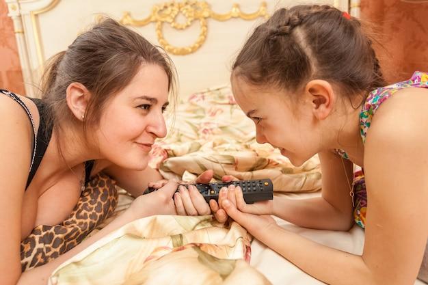 Closeup retrato de duas irmãs olhando uma para a outra e puxando o controle remoto da tv