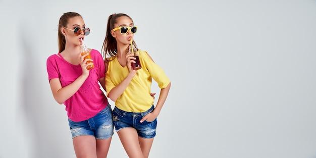 Closeup retrato de duas pessoas simpáticas fofas fascinantes amáveis atraentes encantadoras alegres meninas em roupas casuais com bebida isolada sobre fundo branco