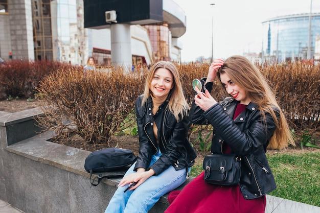 Closeup retrato de estilo de vida de verão de duas melhores amigas rindo e conversando ao ar livre na rua no centro da cidade. vestindo elegante jaqueta preta, vestido, óculos de sol. aproveitando o tempo juntos.