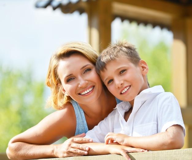 Closeup retrato de feliz mãe e filho olhando para a câmera no parque.