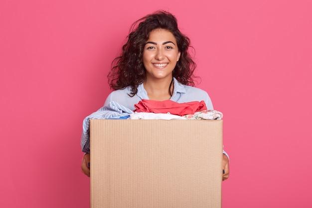Closeup retrato de feliz mulher morena caucasiana, segurando a caixa com doação