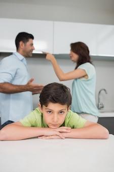 Closeup retrato de filho triste enquanto os pais se brigam