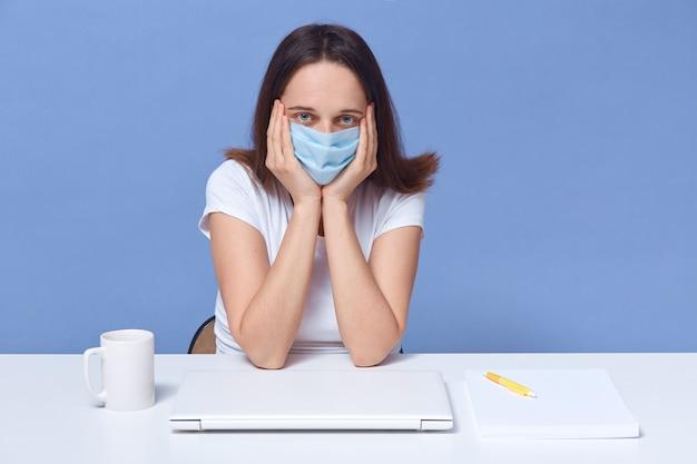 Closeup retrato de freelancer cansado, vestindo camiseta branca e máscara médica, senhora sentada à mesa, mantendo as mãos sob o queixo