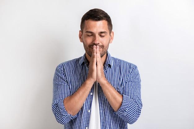Closeup retrato de homem bonito faz um gesto de oração. - gesto de conceito