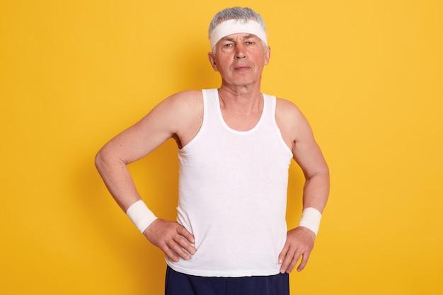 Closeup retrato de homem idoso com as mãos nos quadris, vestindo camiseta branca sem mangas e bandana fazendo esportes