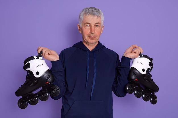 Closeup retrato de homem sênior estar pronto para andar de patins ao ar livre.
