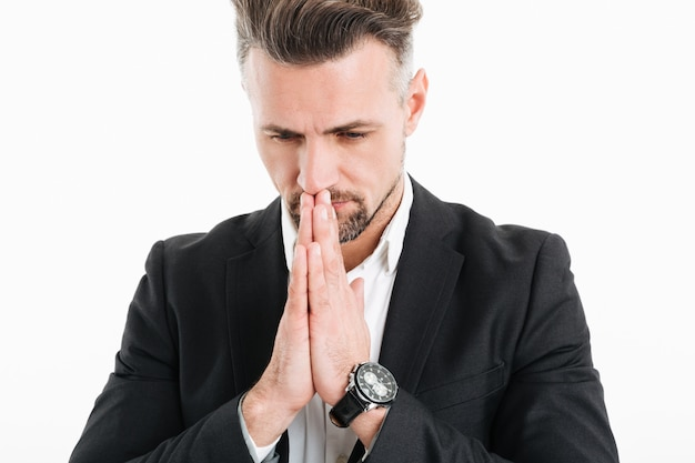 Closeup retrato de homem sério concentrado vestindo jaqueta preta, juntando as palmas das mãos para rezar, isolado sobre o branco