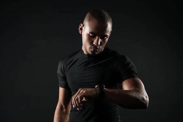 Closeup retrato de homem sério esportes afro-americanos, verificando o tempo na mão