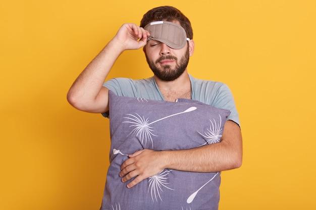 Closeup retrato de homem sonolento com venda nos olhos, segurando o travesseiro nas mãos, abre a máscara de dormir, mantendo os olhos fechados